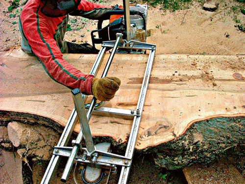 Chainsaw attached to rail making plank cuts
