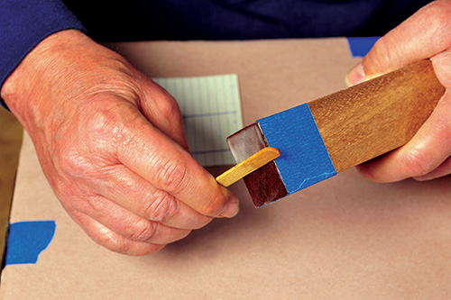 Using a popsicle stick to scrape off extra epoxy from board end