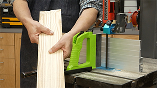 man holding two matching boards next to a band saw