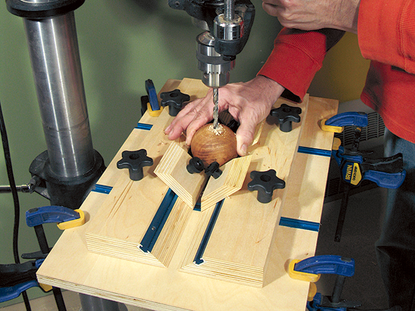 Drill press jig for drilling holes in round objects
