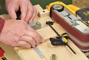 Using a belt sander to make adjustments to band saw blade guide