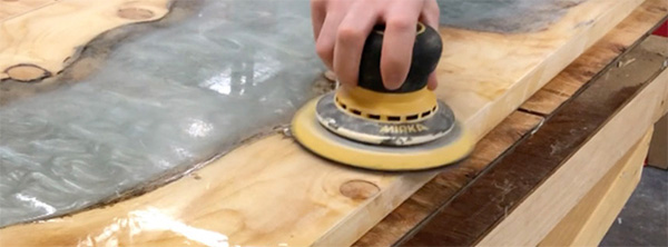 Using a random orbit sander to sand epoxy table surface