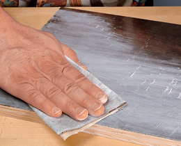 Sanding across wood treated with wood sealer