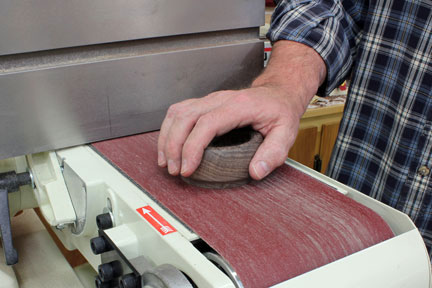 Sanding paper residue off of glue block with a belt sander