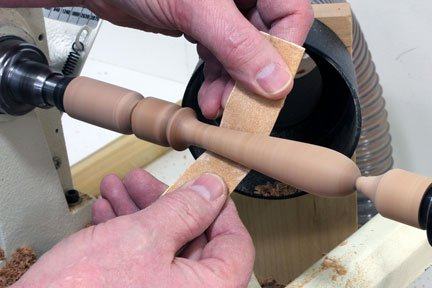 Sanding down spindle at a lathe