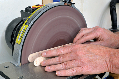 Using sander to smooth out sides of tongs