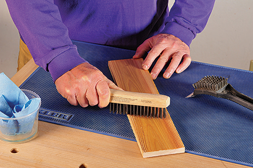 Using a wire brush to scrape black and white paint on a board for barnwood finish