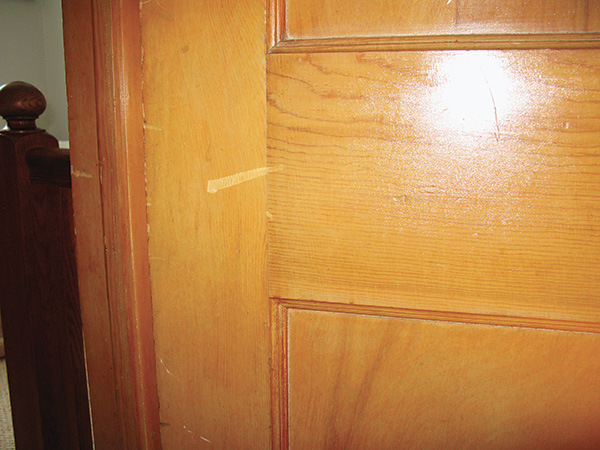 Close-up of a scratch in lacquer finish on door