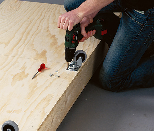 Installing casters to the base of coffee table bed