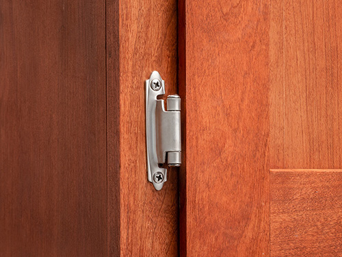 Cabinet door with installed semi-concealed hinge