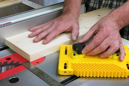 Setting featherboard on table saw before cut