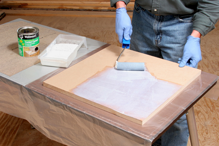 Rolling contact cement on back of laminate sheet