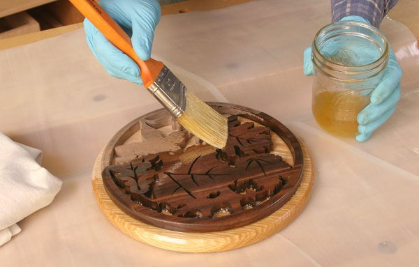 Brushing a polyurethane and mineral oil finish on a round trivet