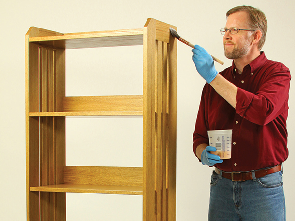 Applying stain to a bookshelf