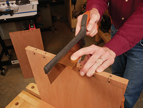 Using a dovetail saw to cut out waste around dovetail pins