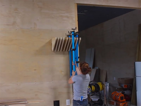 April Wilkerson organizes her bar clamps on the shop wall