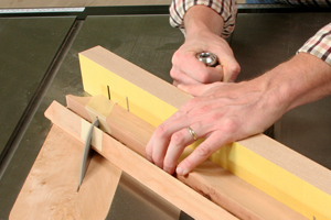 Cutting through a table saw jig with sandpaper adhered to it