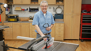 man standing next to table saw