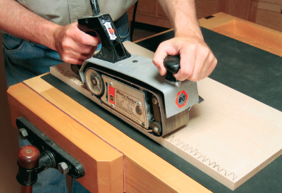 Using a belt sander to sand edging flush with base