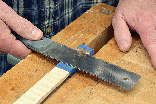 Using hand saw to cut accent dowel in tongs base