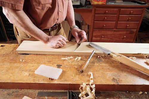 Using a card scraper to shave a board