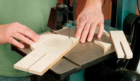 Using a band saw to cut the circular baseplate of the jig