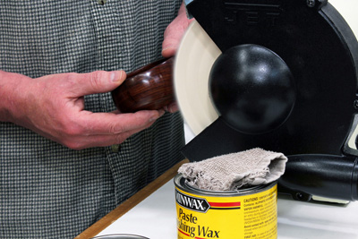 Buffing a wax finish with a cloth buffing wheel in grinder