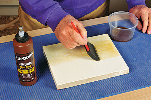 Applying hide glue to the surface of a board