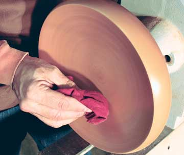 Applying friction polish to a turned maple bowl