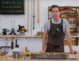 Man standing in front of workshop bench with two chisels laying in front of him